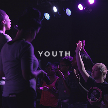 Church on the Rock Youth Ministry: a youth worship service with audience members raising their hands in praise