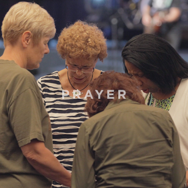 Chuch on the Rock Prayer Ministry: four women with heads bowed in prayer